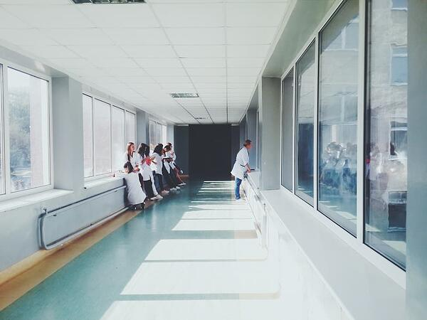 woman-in-white-shirt-standing-near-glass-window-inside-room-127873